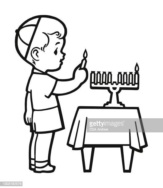 Boy Lighting a Candle on a Menorah