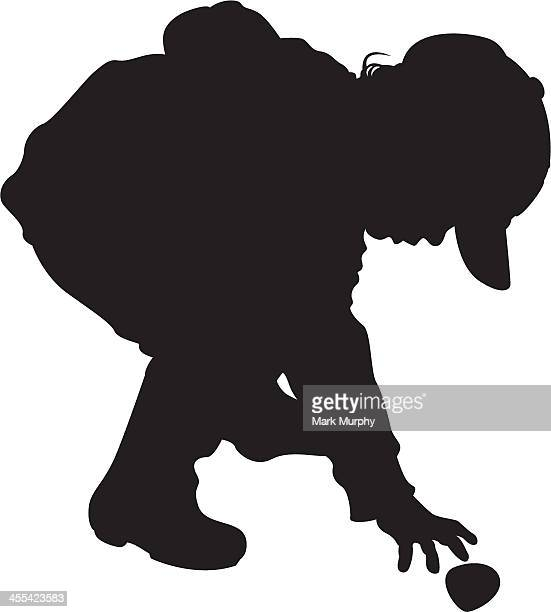 Boy Picking up Stone in Silhouette