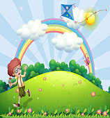 boy playing and his kite at the hilltop with rainbow