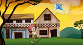 boy playing with his kite in front of wooden barnhouses