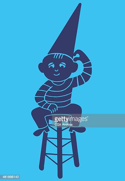 ilustraciones, imágenes clip art, dibujos animados e iconos de stock de boy wearing dunce cap sitting on stool - pintura rupestre