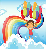 boy with balloons standing near the rainbow