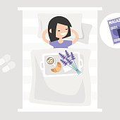 Breakfast in bed. Top view. Coffee, croissant and a bouquet of lavender flowers on a tray. Romantic relationships concept. Young character lying in bed. Flat 2.0 editable vector illustration, clip art