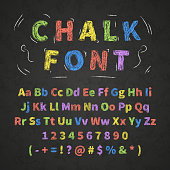 Bright colorful retro hand drawn alphabet letters drawing with chalk on black chalkboard