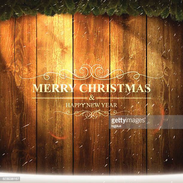 Bright Merry Christmas lettering on Wooden Background with garland, snow
