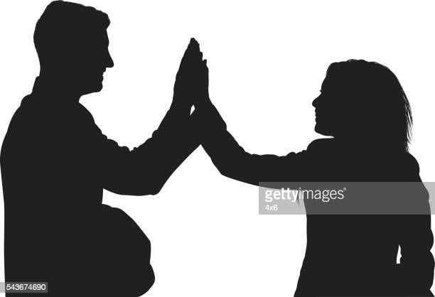 Business couple giving high five