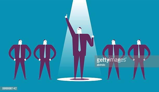 Business man raises his fist in a spotlight.