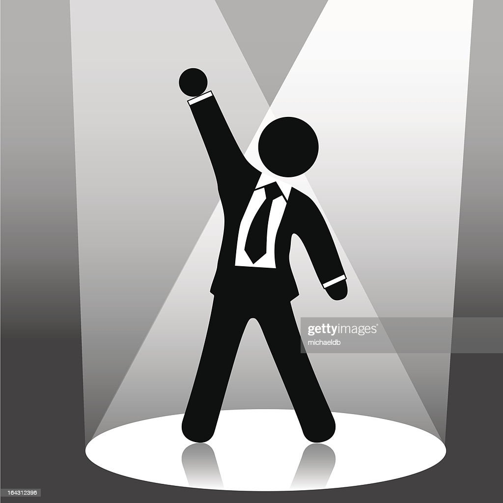 business man symbol raises fist celebration on stage in spotlight