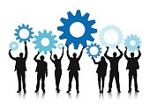 Business people holding gears