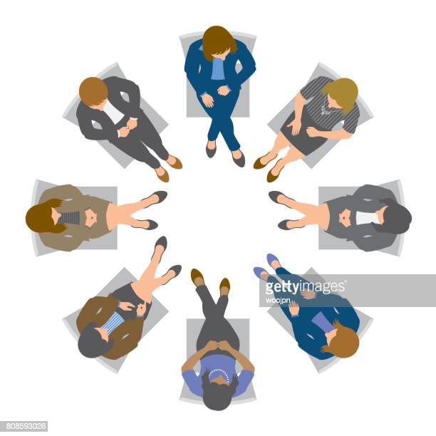 Business women sitting in circle and discussing from above