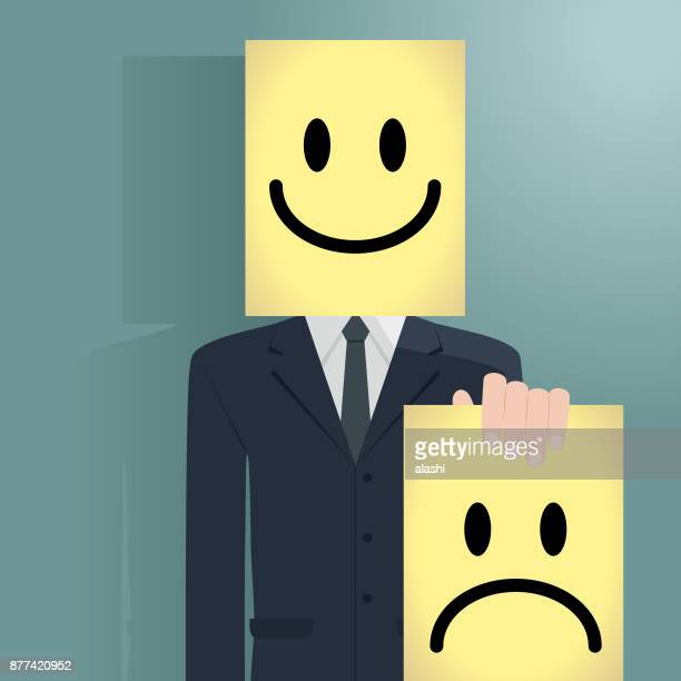 Businessman behind a happy mask holding an unhappy mask
