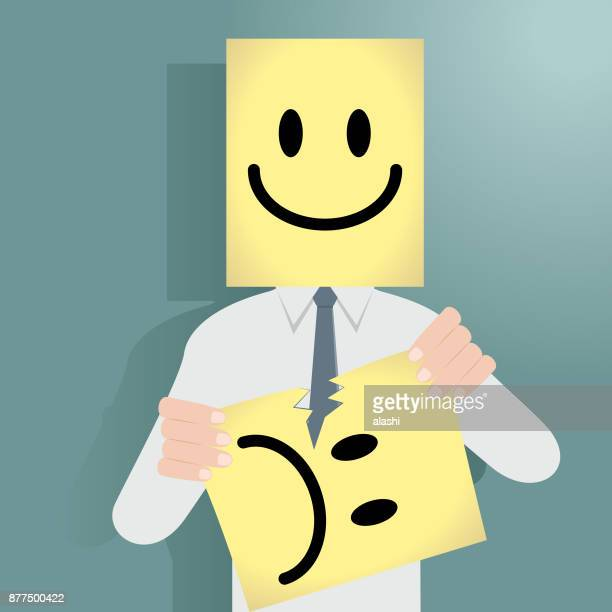 Businessman behind a happy mask tearing an unhappy mask