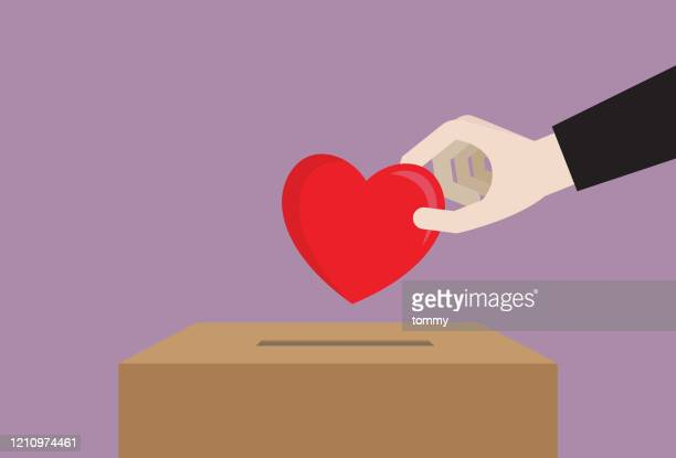 businessman drops a heart in a donation box - giving tuesday stock illustrations
