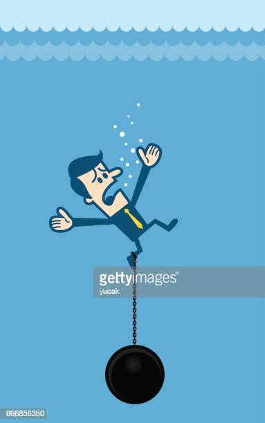 Businessman drowning chained with a weight