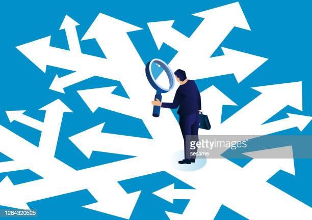 複雑な矢印の道に立って虫眼鏡を持ち、選択をするビジネスマン - 迷う点のイラスト素材/クリップアート素材/マンガ素材/アイコン素材