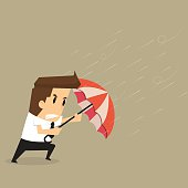 businessman holding an umbrella in the middle of a rainstorm
