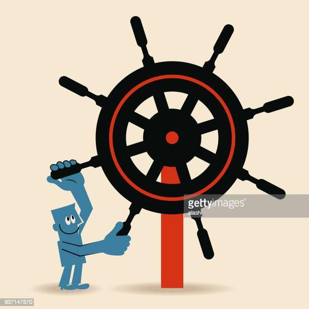 Businessman (Captain) holding big rudder