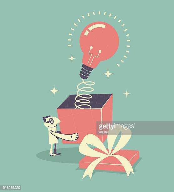 Businessman holding gift box with idea light bulb with spring