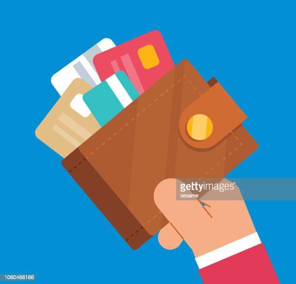 businessman holding wallet full of credit cards - wallet stock illustrations