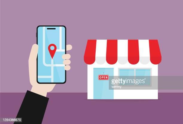 illustrazioni stock, clip art, cartoni animati e icone di tendenza di l'uomo d'affari tiene un telefono cellulare per trovare una sede del negozio - motore di ricerca