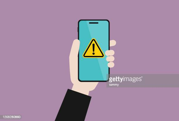 businessman holds a mobile phone with a warning sign - computer virus stock illustrations