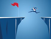 Businessman jump through the gap obstacles between hill to red flag and success. Running and jump over cliffs. Business risk and success concept.