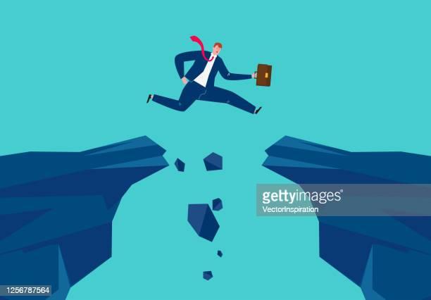 stockillustraties, clipart, cartoons en iconen met zakenman die van één rots aan een andere springt, die moeilijkheden, uitdagingen, succesvol bedrijfsconcept overwint - zakenman