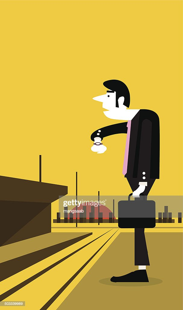 Businessman looking watch and standing at a train station.