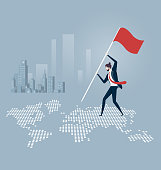 Businessman putting a flag and standing on top of a world map