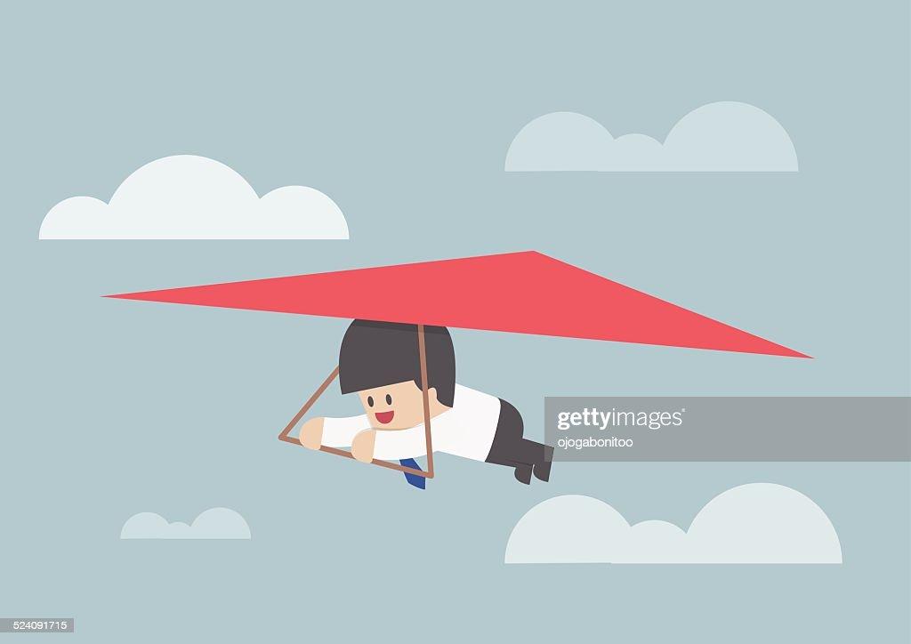 Businessman riding a hang glider