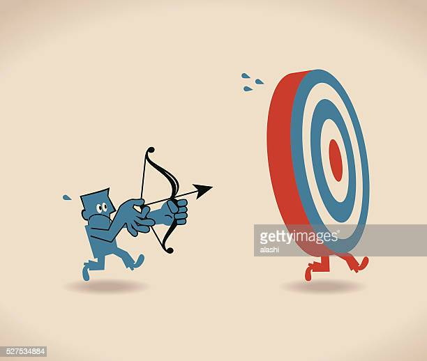 Businessman running to catch target, trying to shoot at bulls-eye