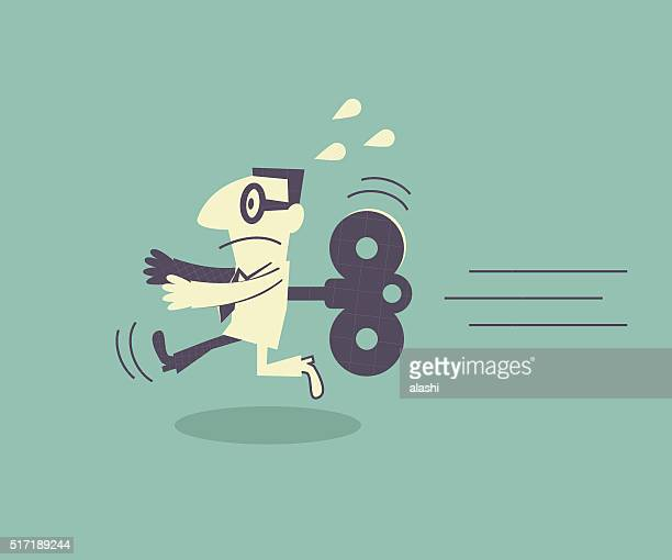 Businessman running with wind-up key in his back
