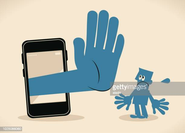 Businessman standing in front of a big smart phone, a big hand from the mobile phone making stop gesture