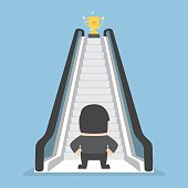 Businessman standing in front of escalator that leads the trophy