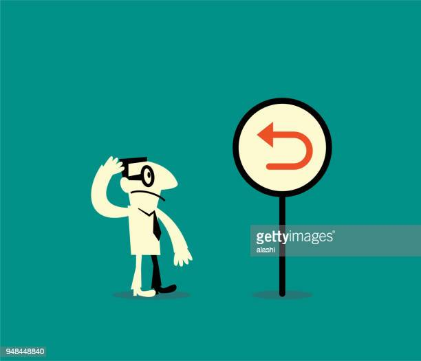 businessman standing in front of the back arrow sign - refusing stock illustrations, clip art, cartoons, & icons