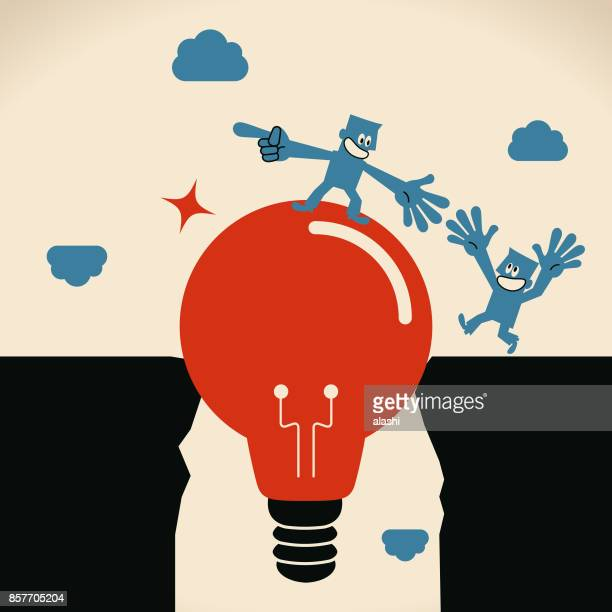 Businessman (Leader) standing on a big idea light bulb bridge and helping another man to cross cliffs (abyss)