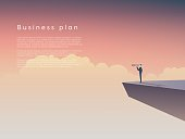 Businessman standing on a cliff above clouds with monocular. Business
