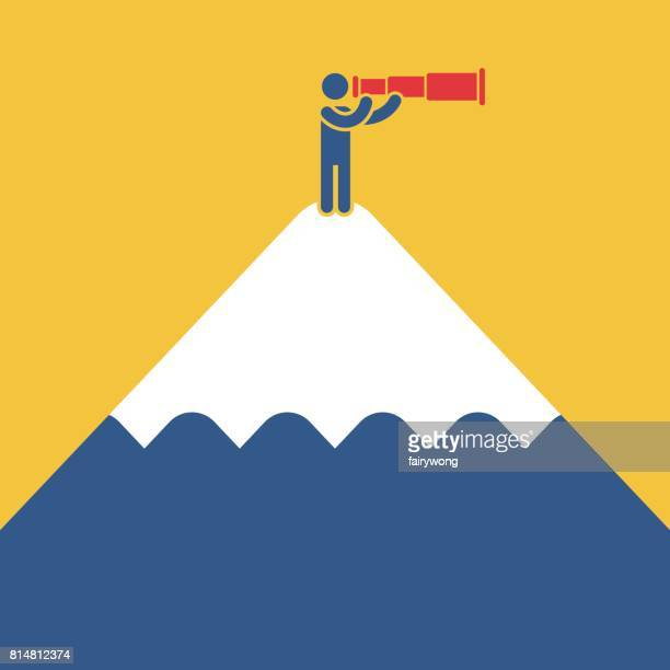 Businessman standing on top of a mountain looking into the telescope