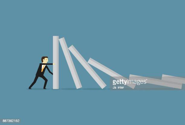 businessman stopping domino effect - domino effect stock illustrations