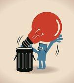 Businessman throwing a big idea light bulb in a garbage (trash) can