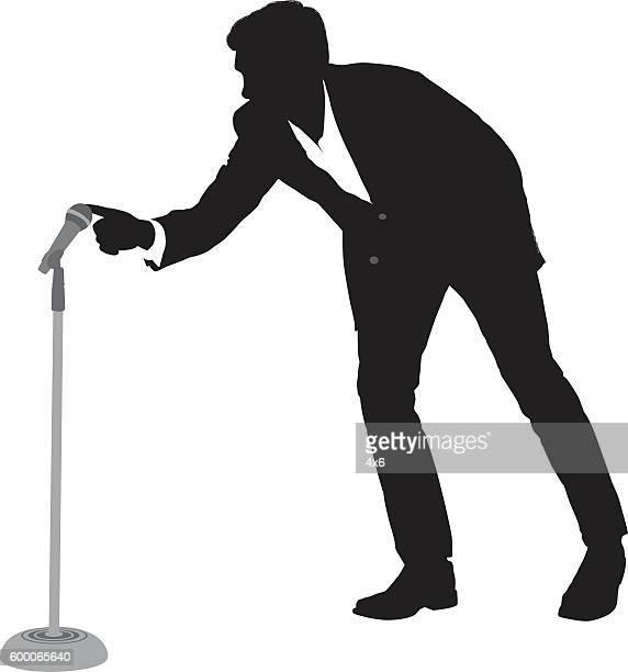 businessman touching the microphone - マイクスタンド点のイラスト素材/クリップアート素材/マンガ素材/アイコン素材