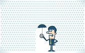 Businessman under a little umbrella in the rain