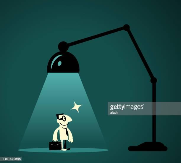 illustrazioni stock, clip art, cartoni animati e icone di tendenza di uomo d'affari con valigetta in piedi davanti alla lampada da scrivania (spotlight) - guida turistica professione