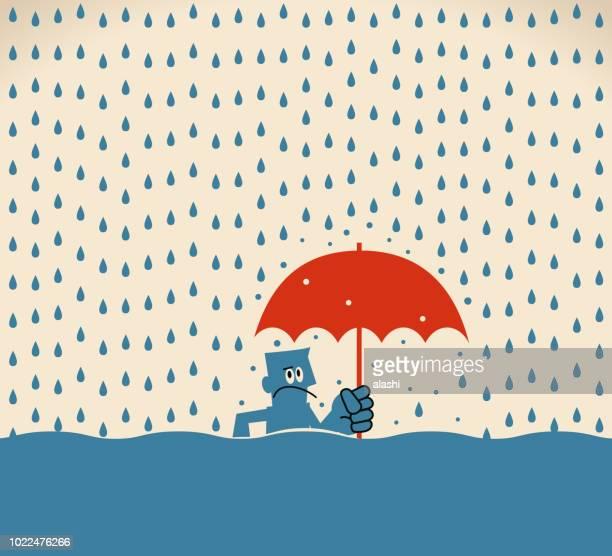 雨の洪水に傘立って実業家
