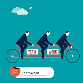 Businessmen on tandem bike with team work word