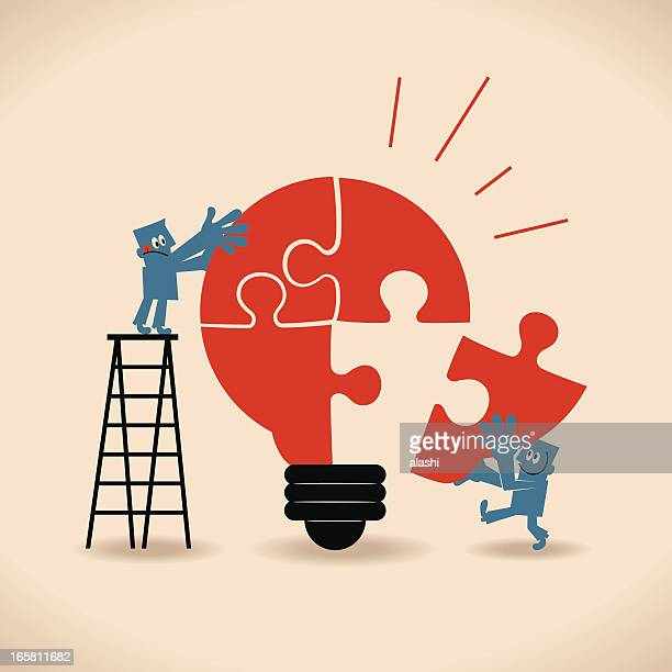Businessmen standing on ladder, completing an idea light bulb puzzle