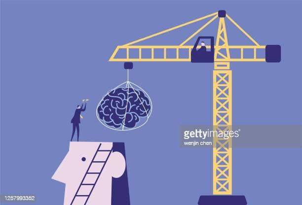 ビジネスマンは、巨人のための脳をインストールするためにクレーンを使用しています - 建物の骨組み点のイラスト素材/クリップアート素材/マンガ素材/アイコン素材