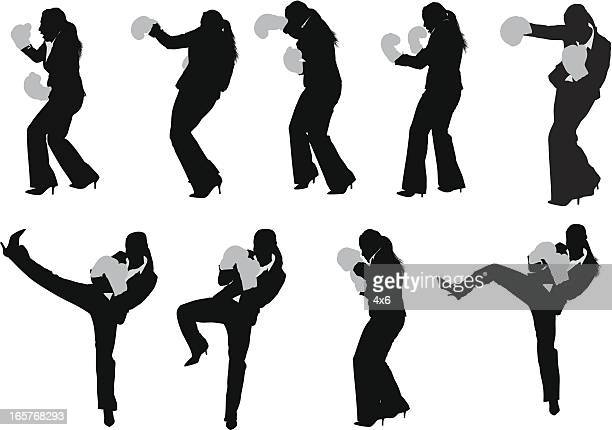 Businesswoman kick boxing in pant suit