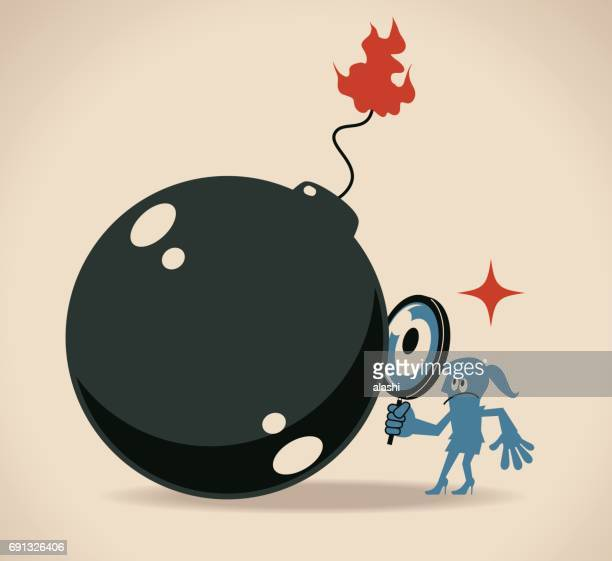 Businesswoman (woman, girl) looking at a big bomb with a magnifier