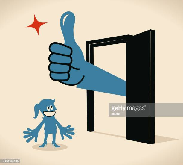 Businesswoman standing in front of a door, big hand out from the door with thumbs up gesture